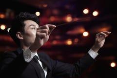 Młody dyrygent z batutą podnoszącą przy występem obrazy royalty free