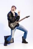 Młody ekspresyjny rockowy muzyk bawić się gitarę elektryczną i śpiew Gwiazda rocka robi rockowemu gestowi obrazy royalty free