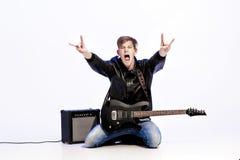 Młody ekspresyjny rockowy muzyk bawić się gitarę elektryczną i śpiew Gwiazda rocka robi rockowemu gestowi fotografia stock