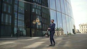Młody elegancki biznesmen chodzi wzdłuż ulicy na nowożytnym budynku tle zbiory wideo