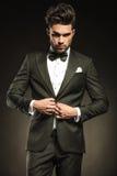 Młody elegancki biznesowy mężczyzna układa jego smoking obraz stock