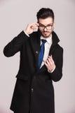 Młody elegancki biznesowy mężczyzna załatwia jego szkła Zdjęcia Royalty Free