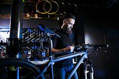 Młody elegancki brodaty mężczyzna z długie włosy Kaukaskim męskim mechanika pracownikiem przy rowerowym warsztatem używa narzędzi obraz stock
