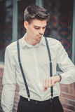 Młody elegancki mężczyzna model patrzeje na jego zegarku Zdjęcia Royalty Free