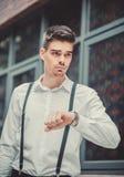 Młody elegancki mężczyzna model patrzeje na jego zegarku Fotografia Royalty Free