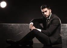 Młody elegancki mężczyzna w kostiumu i krawata łgarskim puszku Zdjęcia Royalty Free