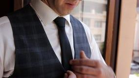 Młody elegancki mężczyzna wiąże krawat w białej koszula stoi, ?lubni przygotowania zbiory