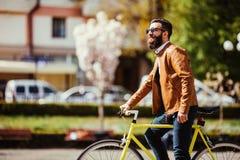 Młody elegancki modniś pozuje obok jego bicyklu na miasto ulicie zdjęcia stock