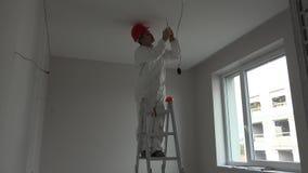 Młody elektryk instaluje dymnego detektoru pożarniczego alarm na suficie zbiory