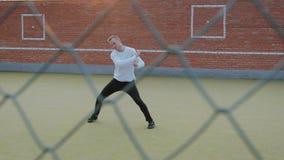 Młody energiczny facet, uliczny tancerz w czerni spodniach i biały pulower, wykonuje pięknych ruchy na zbiory wideo