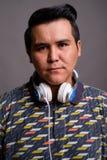 Młody etniczny mężczyzna jest ubranym hełmofony przeciw szaremu backgroun zdjęcia royalty free
