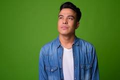 Młody etniczny mężczyzna jest ubranym mądrze odzież przeciw zielonemu tłu obraz stock
