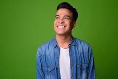 Młody etniczny mężczyzna jest ubranym mądrze odzież przeciw zielonemu tłu fotografia stock