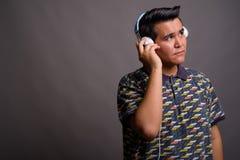 Młody etniczny mężczyzna słucha muzyka przeciw szaremu backgroun zdjęcia stock