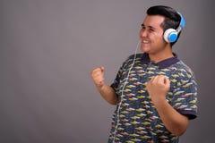 Młody etniczny mężczyzna słucha muzyka przeciw szaremu backgroun obraz stock