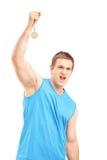 Młody euforyczny sportowiec trzyma złotego medal Fotografia Royalty Free