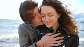 Młody Europejski mężczyzna całuje policzek dziewczyny przy morzem w burzy przy zmierzchem, zwolnione tempo zbiory wideo