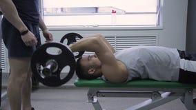 Młody facet ćwiczy z barbell pod trener kontrola w gym zbiory wideo