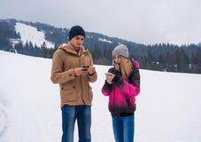 Młody facet i dziewczyna który patrzeją ich smartphones przeciw zdjęcia stock