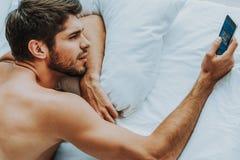 Młody facet kłaść w łóżku z telefonem komórkowym obraz royalty free