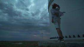 Młody facet obok silników wiatrowych, produkuje ekologiczną energię Pojęcie zanieczyszczenie środowiska, nowy zdjęcie wideo