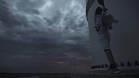 Młody facet obok silników wiatrowych, produkuje ekologiczną energię Pojęcie zanieczyszczenie środowiska, nowy zbiory wideo