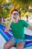 Młody facet opowiada na telefonie i relaksuje wewnątrz Fotografia Royalty Free