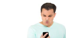 Młody facet patrzeje gniewny przy jego telefonem komórkowym obraz royalty free