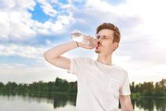 Młody facet pije świeżą wodę przeciw jeziornemu i lasowemu tłu lata pragnienia facet chce pić fotografia stock