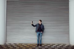 Młody facet robi selfie fotografii przeciw tłu metalu drzwi Zdjęcie Stock