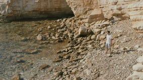 Młody facet rzuca kamienie up w rękach na linii brzegowej zdjęcie wideo