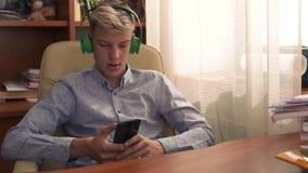 Młody facet siedzi w rzemiennym krześle i słucha muzyka zdjęcie wideo