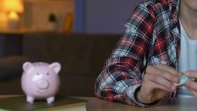 Młody facet stawia dolarowych rachunki w prosiątko banku, wymarzeni oszczędzania, planuje budżet zbiory wideo