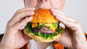 Młody facet trzyma świeżego hamburger Bardzo głodny uczeń je fast food Gorący pomocniczo jedzenie Pojęcie obżarstwo i unhealt zdjęcie royalty free