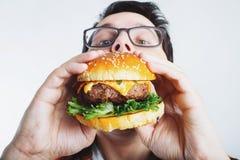 Młody facet trzyma świeżego hamburger Bardzo głodny uczeń je fast food Gorący pomocniczo jedzenie Pojęcie obżarstwo i unhealt zdjęcie stock