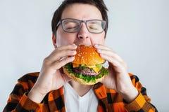 Młody facet trzyma świeżego hamburger z szkłami Bardzo głodny uczeń je fast food Gorący pomocniczo jedzenie Pojęcie obżarstwo a obrazy royalty free