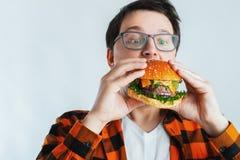 Młody facet trzyma świeżego hamburger z szkłami Bardzo głodny uczeń je fast food Gorący pomocniczo jedzenie Pojęcie obżarstwo a zdjęcie royalty free