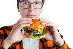 Młody facet trzyma świeżego hamburger z szkłami Bardzo głodny uczeń je fast food Gorący pomocniczo jedzenie Pojęcie obżarstwo zdjęcie stock