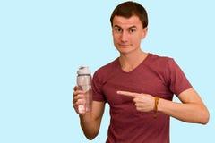 Młody facet trzyma butelkę woda w jego ręce zdjęcia stock
