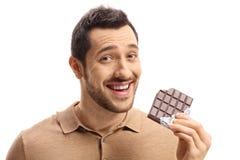 Młody facet trzyma czekoladowego baru gryźć ono uśmiecha się i zdjęcia royalty free