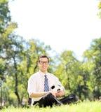 Młody facet trzyma futbol w parku sadzającym na trawie Zdjęcia Stock
