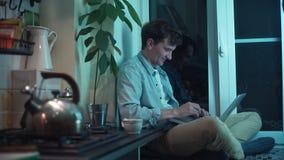Młody facet używa komputerowego obsiadanie przy kuchnią podczas gdy czajnika gotowanie na kuchence zbiory