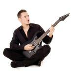 Młody facet ubierający w czerni ubraniach siedzi gitarę i bawić się Zdjęcie Royalty Free