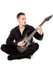 Młody facet ubierający w czerni ubraniach siedzi gitarę i bawić się Obrazy Stock