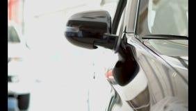 Młody facet uważnie egzamininuje nowego samochód w przedstawicielstwo firmy samochodowej obrazy royalty free