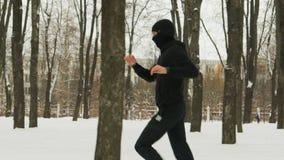 Młody facet w czerń sportach odziewa i Balaclava, wykonuje rozgrzewkę przed trenować w zimy śnieżystym mieście zbiory