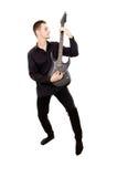 Młody facet w czerni ubraniach bawić się gitarę Obrazy Royalty Free