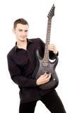 Młody facet w czerni ubraniach bawić się gitarę Fotografia Stock
