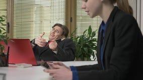Młody facet w kostiumu flirtuje z dziewczyną w biurze, rzuca lasso miłość pojęcie miłość, humor Praca w zbiory wideo