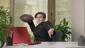 Młody facet w kostiumu siedzi w biurze i próbuje rzucać piłkę dla futbolu amerykańskiego Komedia, humor, sport zdjęcie wideo